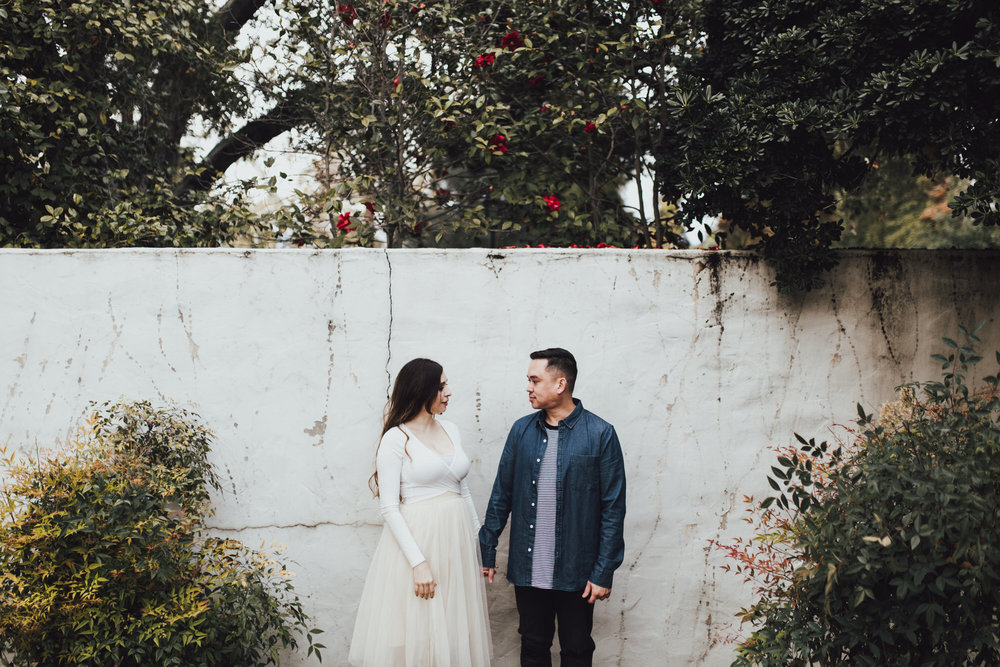 couple against textured white wall with plants