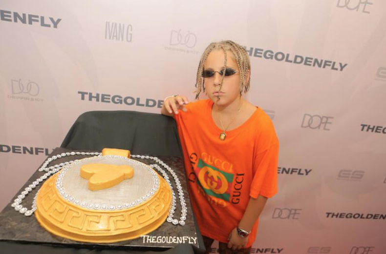 The Golden Fly aka The Drip God Ivan G standing with his celebratory Golden Fly Cake