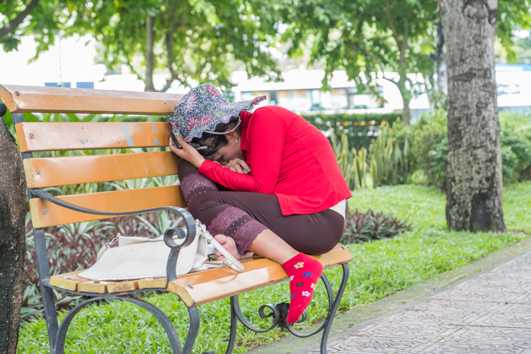 A Vietnamese lady takes an afternoon nap on a park bench in Ho Chi Minh city.