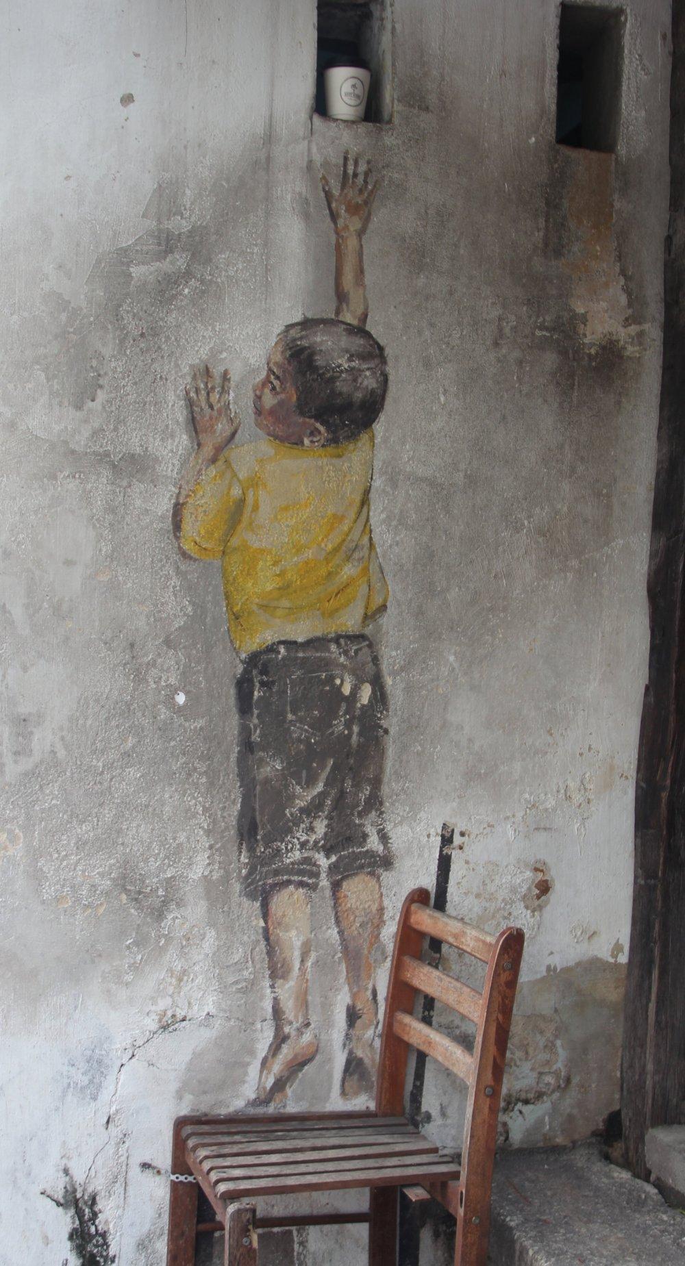 Boy on a chair - A boy reaching for his treasure