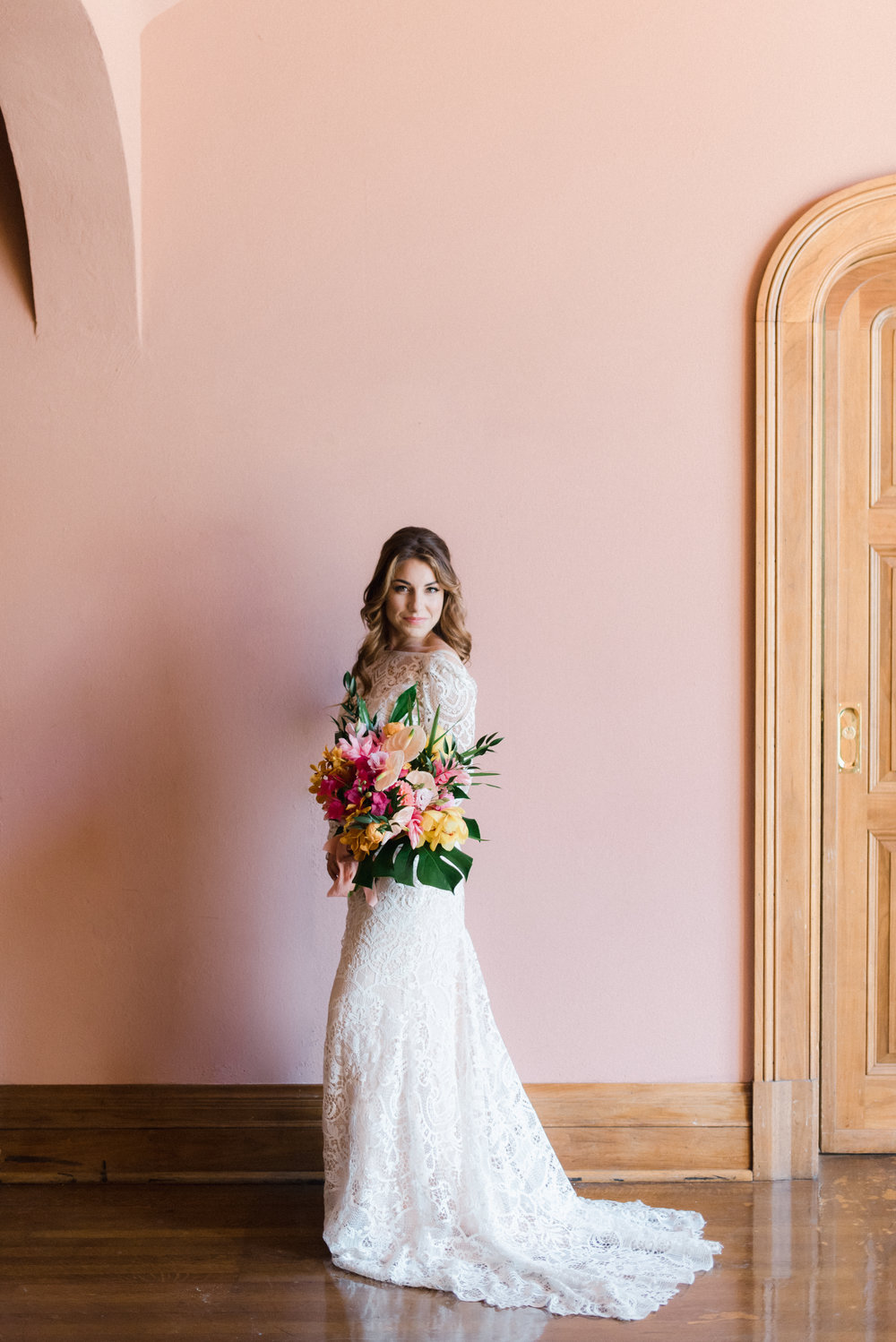 MAxwell house bride against pink wall with big tropical bouquet.jpg