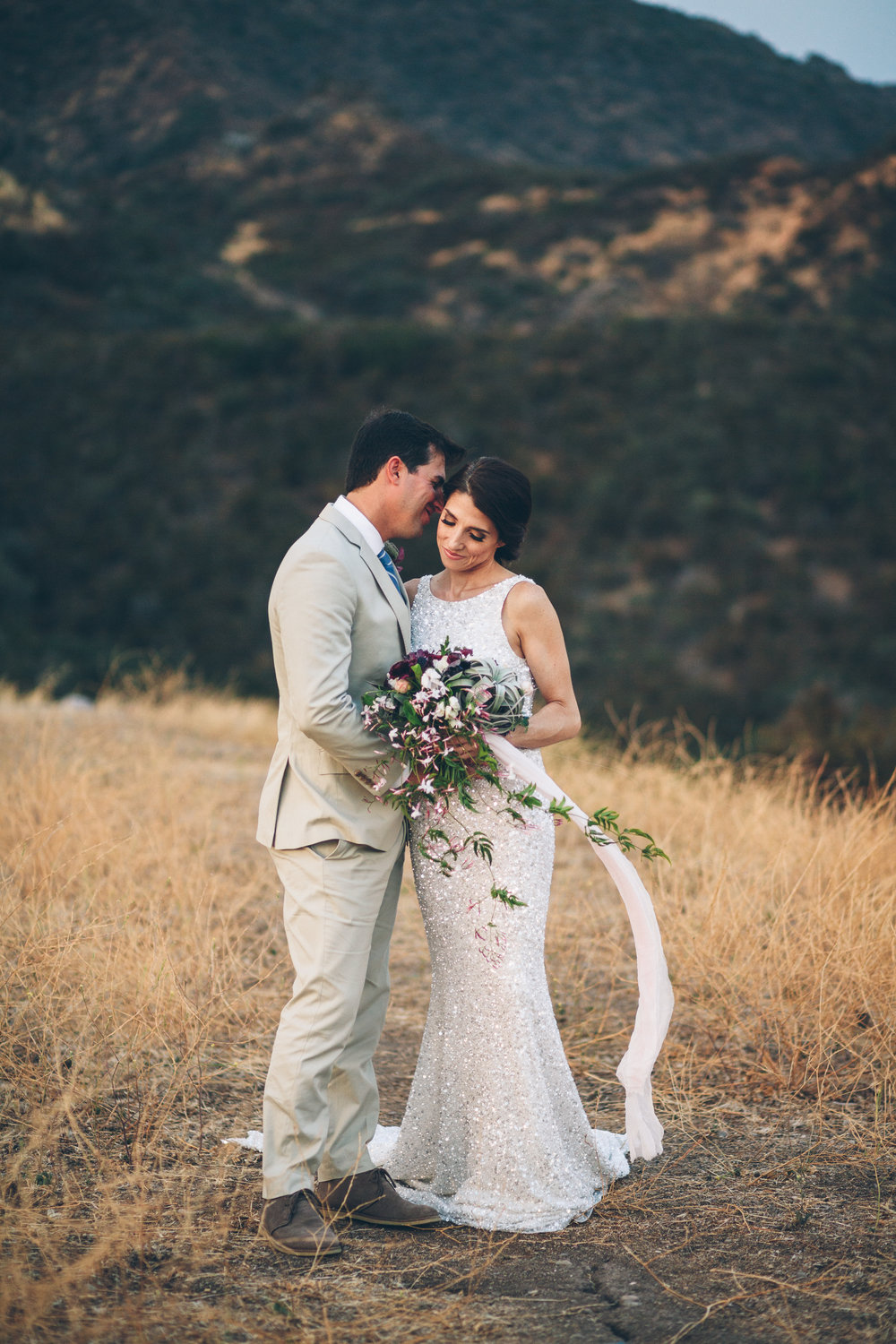 bride and groom in malibu canyon with a flowing wedding bouquet with a blush ribbon and big airplant.jpg