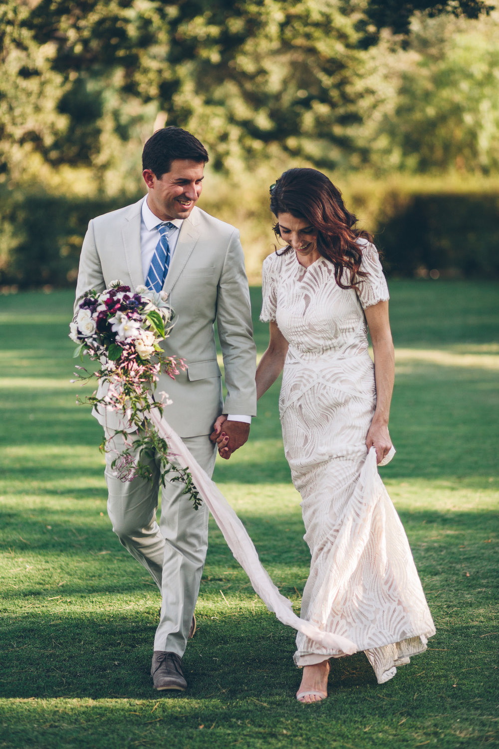 bride and groom walking with long flowing bouquet with blooming jasmine and a long trailing ribbon for a malibu wedding.jpg
