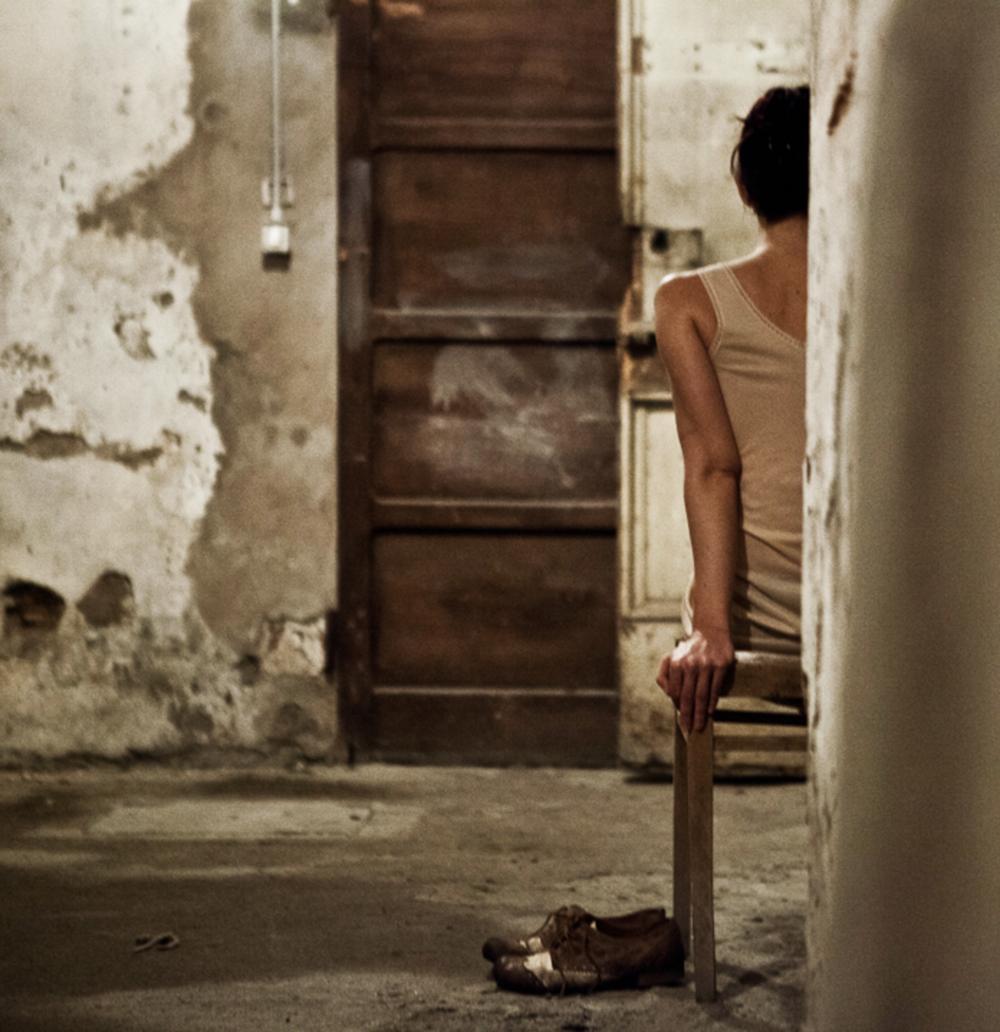 """- Per raccontare la donna, affidandosi esclusivamente alle immagini che ella stessa catturava, traducendole in fotografie e brevi filmati:Eva privata, Eva che si priva.Corpo che si muove in un luogo congelato, in posa, autonomo per solitudine. Eva viva, Eva nuda.Che ascolta musica, che fuma, che si guarda allo specchio, che si veste, che si svela. Eva ed i suoi scatti, in quel brevissimo spazio che separa il suo occhio da una realtà atroce, in una sfida abulica con ciò che l'obiettivo deve catturare.Eva e """"il suo"""" Adolf.Gioca con se stessa, seleziona e trasforma ciò che vuole vedere, sentendone tuttavia l'enorme peso, nutrendolo, crescendolo sino a lasciarsene schiacciare."""