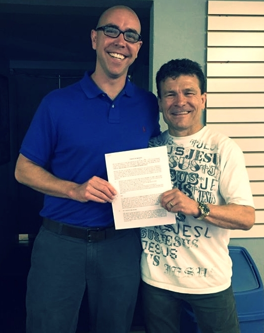 Pastor Brent with Troy Dorsey and the signed lease agreement for our church to meet weekly in the karate studio.