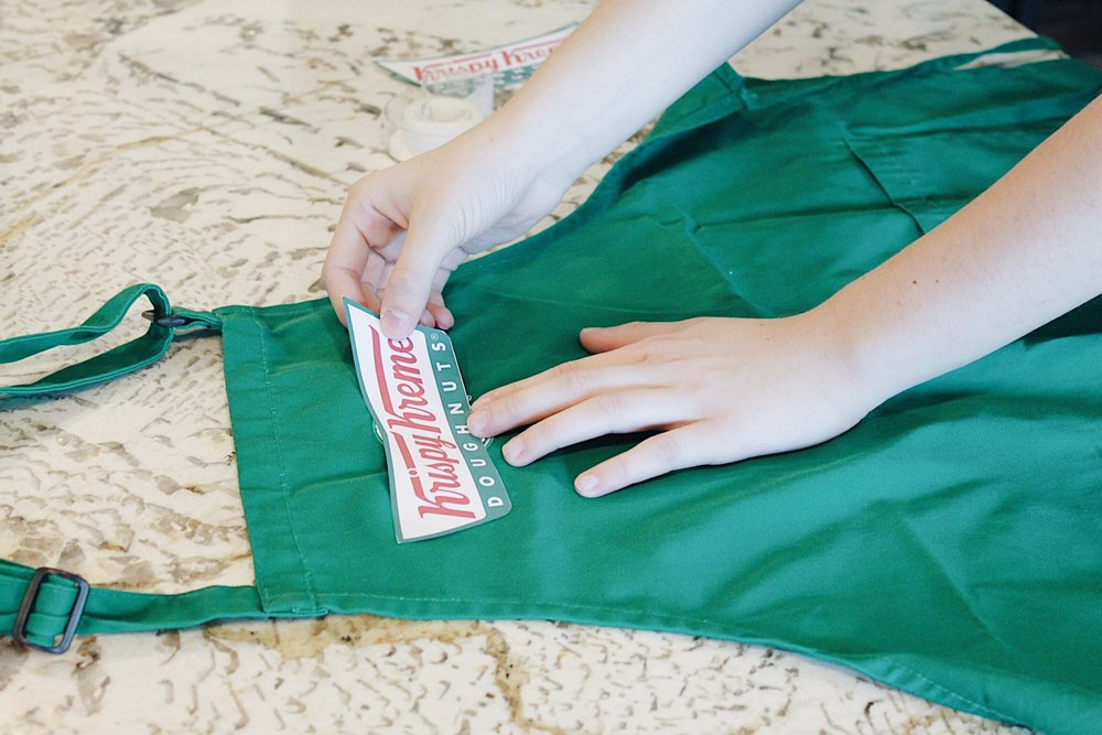 To make the apron, print out a Krispy Kreme logo and tape it onto a plain apron.