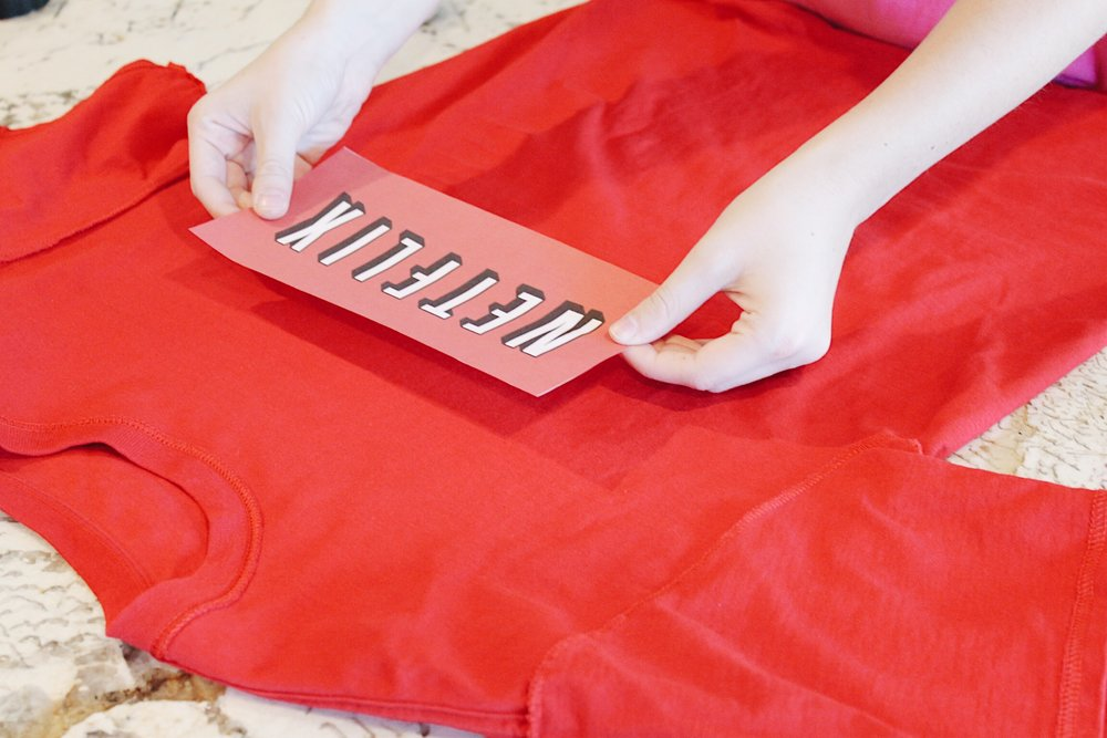 To make the Netflix shirt, print out a Netflix logo and tape it on.