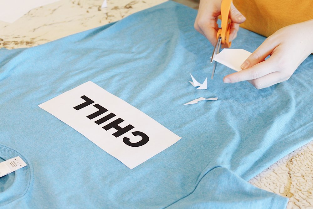 "To make the Chill shirt, print out a paper that says ""Chill"" on it. Then cut up paper snowflakes and tape them on."
