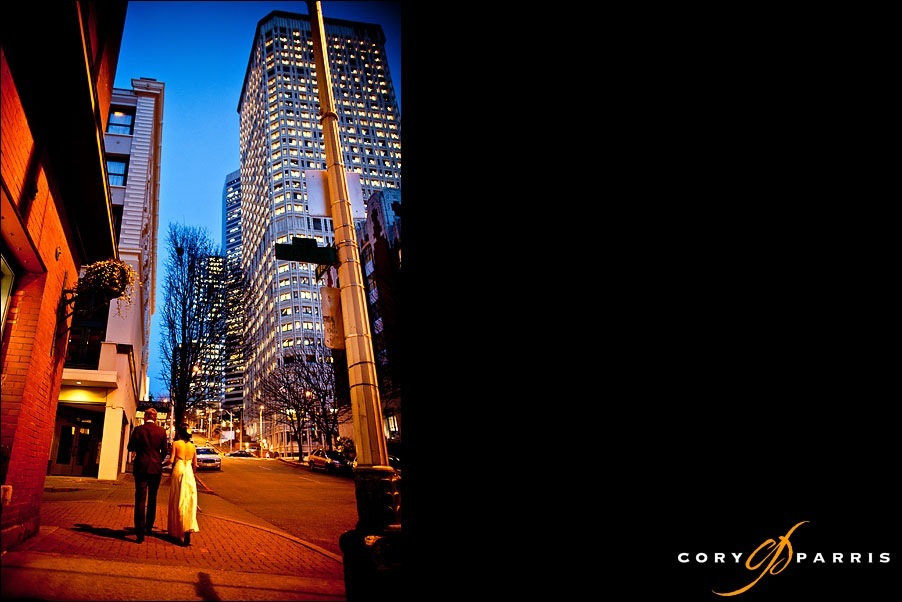 bride and groom walking the seattle streets at night by wedding photographer cory parris