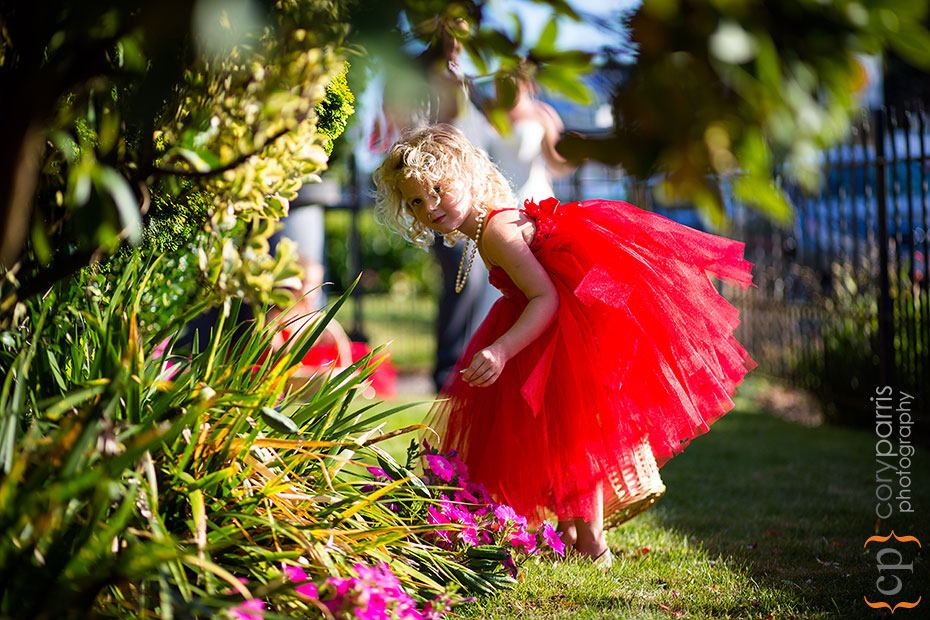 flower girl in red tutu playing in the flowers