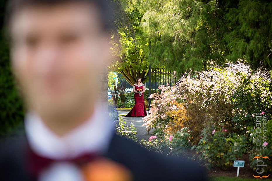 bride in a red dress walking behind groom at woodland park rose garden