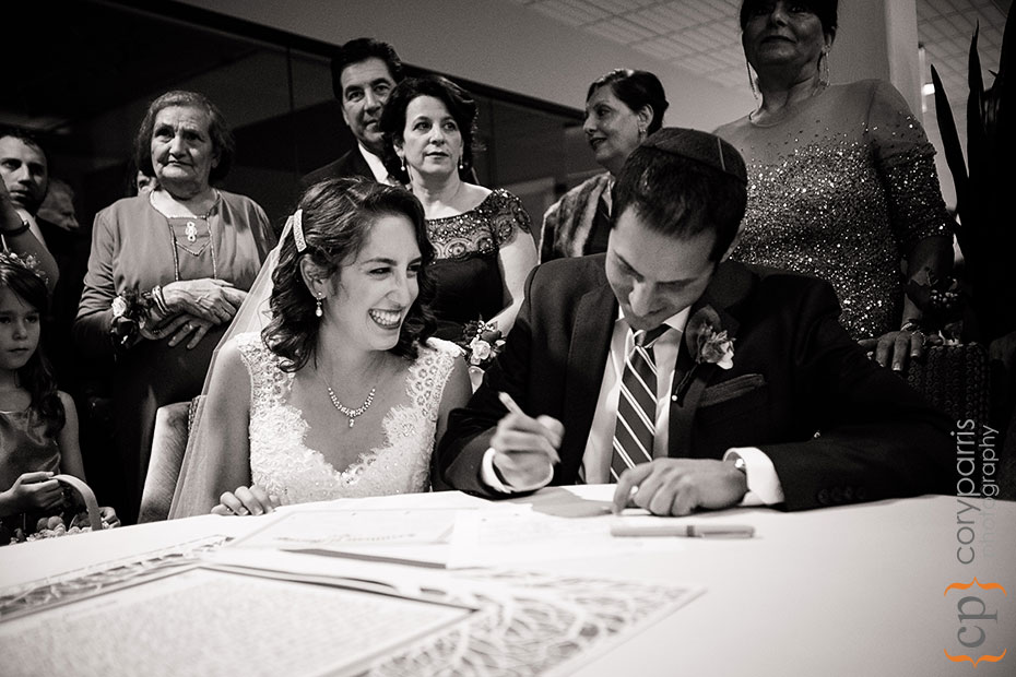 bride and groom signing the Ketubah