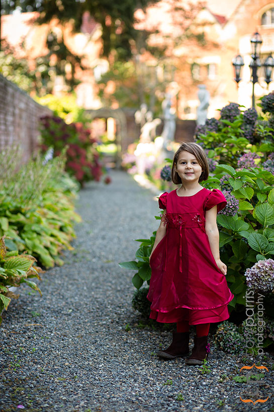 Little girl in red dress in garden