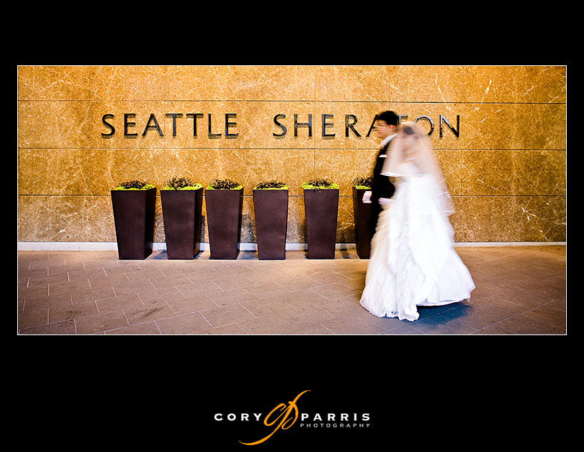 bride and groom walking past the Seattle Sheraton sign