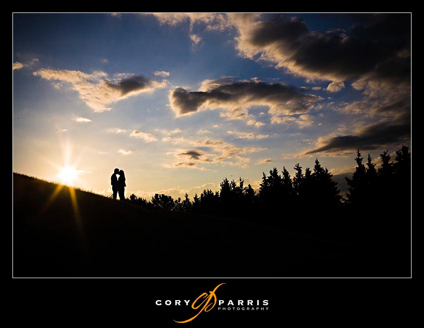 sunset photo of couple on the hill with clouds