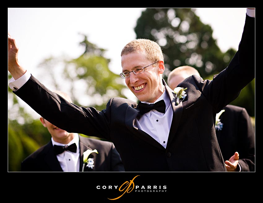 Groom throwing his arms up in celebration after his wedding at the woodland park rose garden in seattle washington as photographed by seattle wedding photographer Cory Parris
