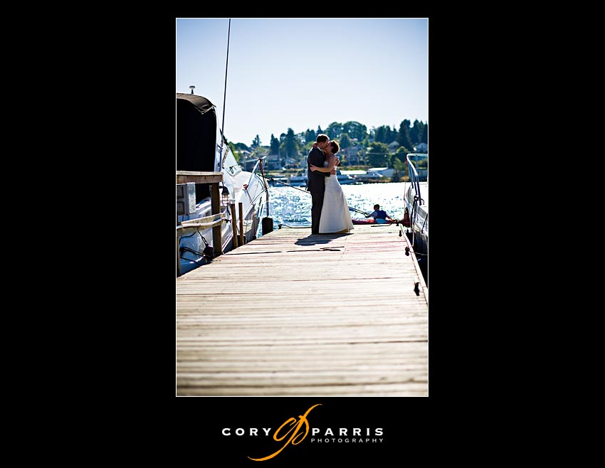 Bride and groom kiss on the dock of the Yacht Club at Lake Union
