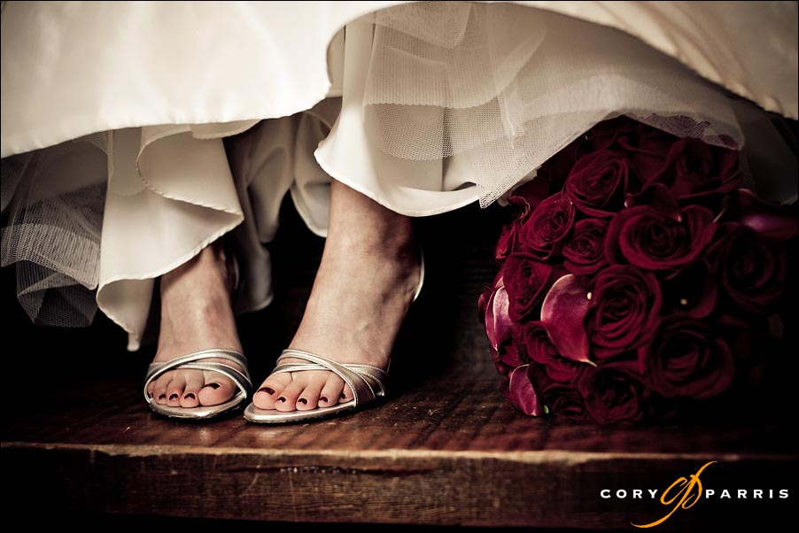 brides feet and shoes with red flowers