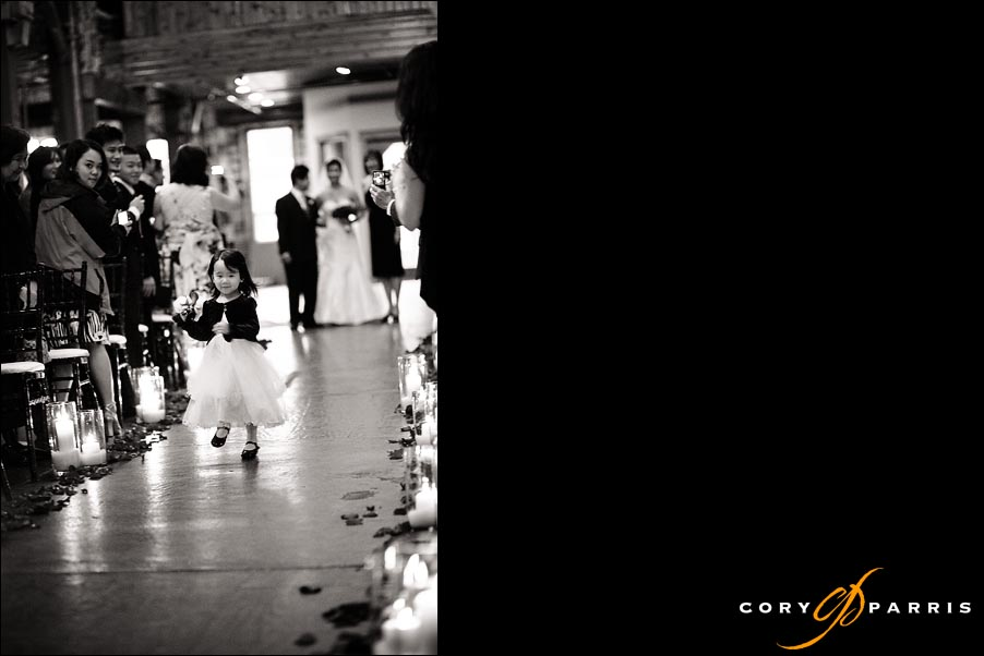 flower girl running down the aisle as the bride watches