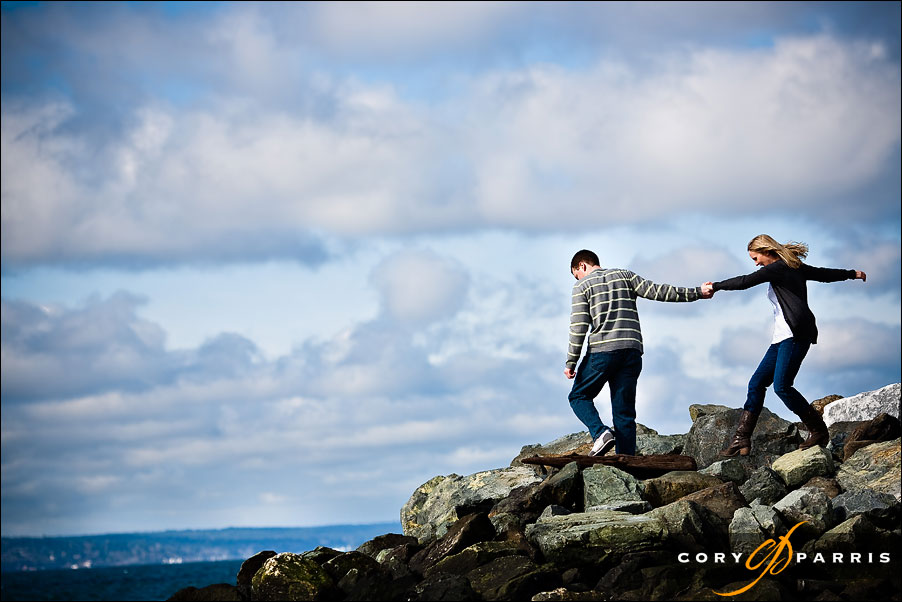 couple walking out onto the rocks with blue sky and clouds behind them in seattle