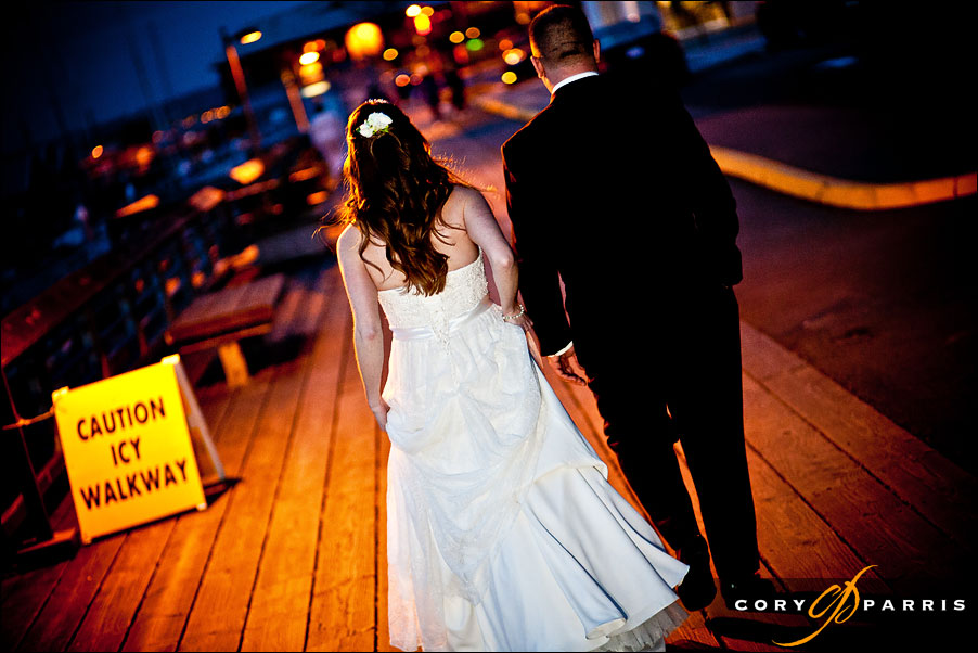 bride and groom walking along the dock in edmonds at night