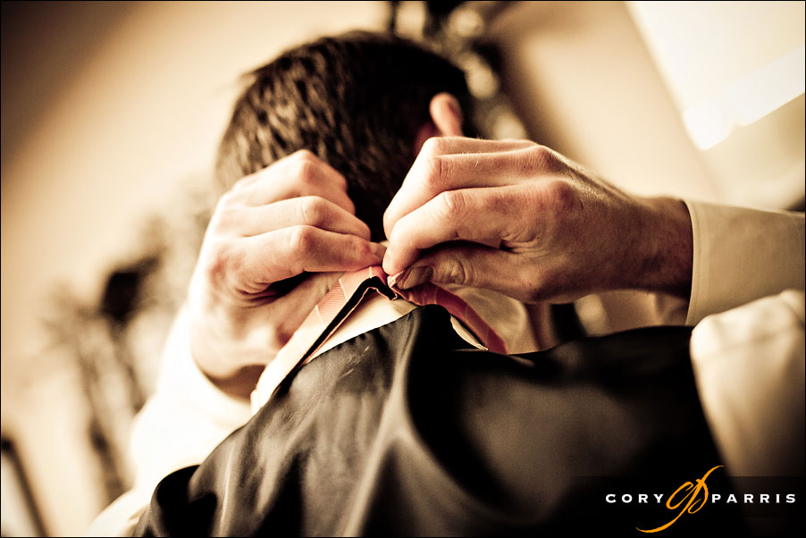 detail of groom putting on his tie by seattle wedding photojournalist cory parris