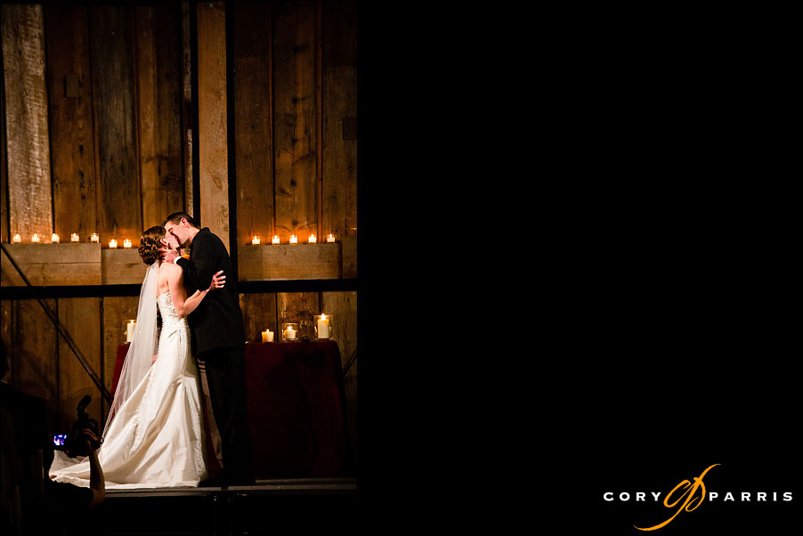 bride and groom's first kiss at pickering barn by seattle wedding photographer cory parris