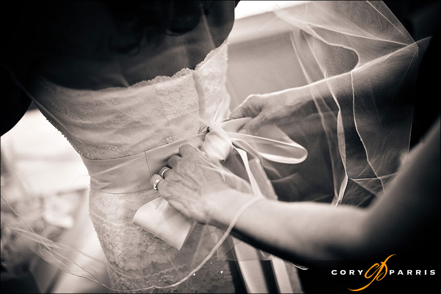tying on the bow on the back of the bride's dress by seattle wedding photographer cory parris