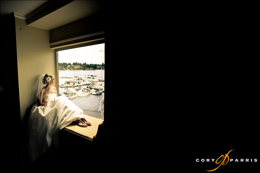 bride sitting in the picture window at the woodmark hotel by wedding photographer in seattle cory parris