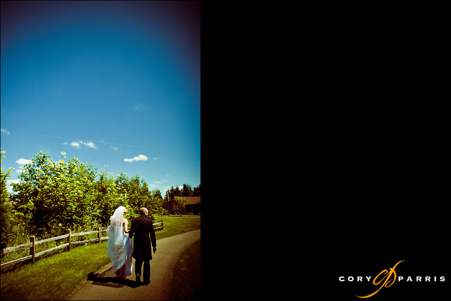 bride and groom walking on a path through the woods by seattle wedding photographer cory parris