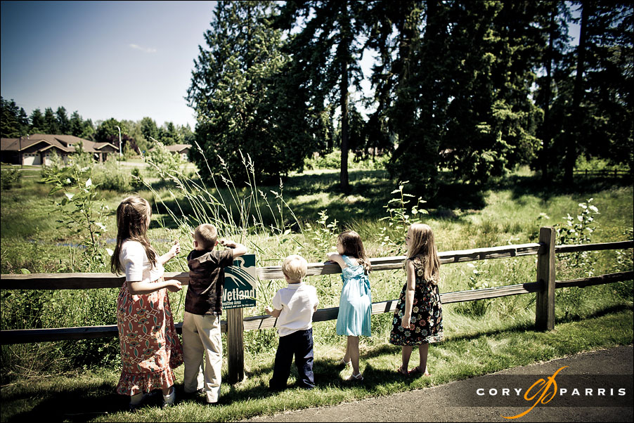 kids looking over a fence by seattle wedding photojournalists cory parris