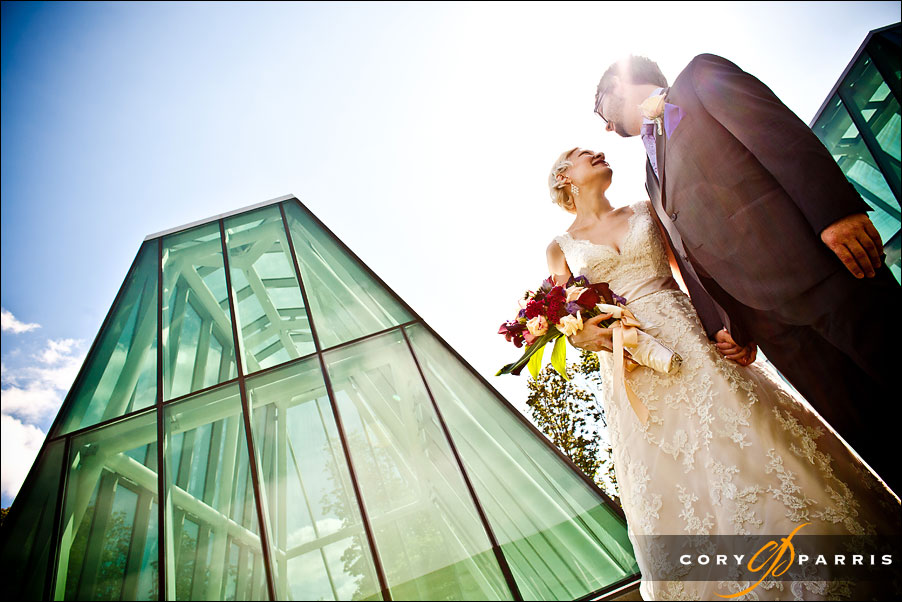 bride and groom near glass structure by seattle wedding photographer cory parris
