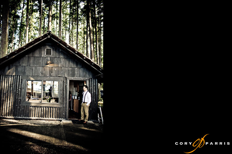 groom standing outside cabin in the woods by seattle wedding photojournalist cory parris