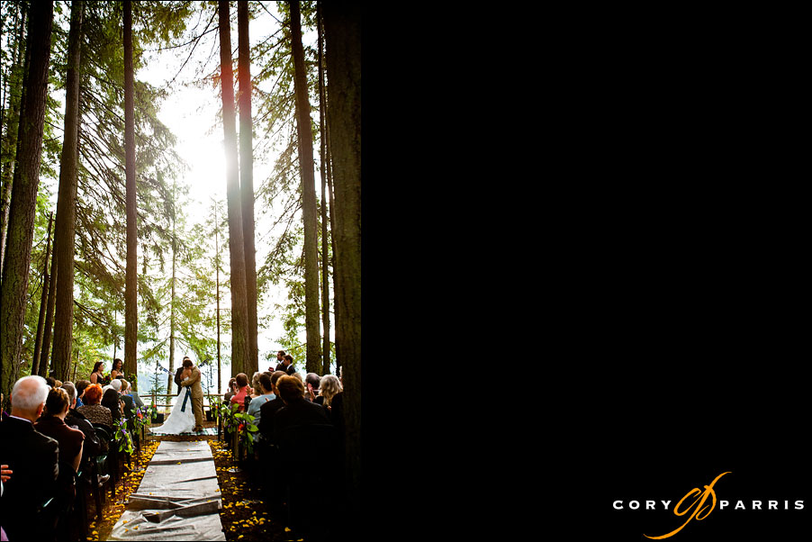 bride and groom kissing during ceremony in the woods by seattle wedding photojournalist cory parris