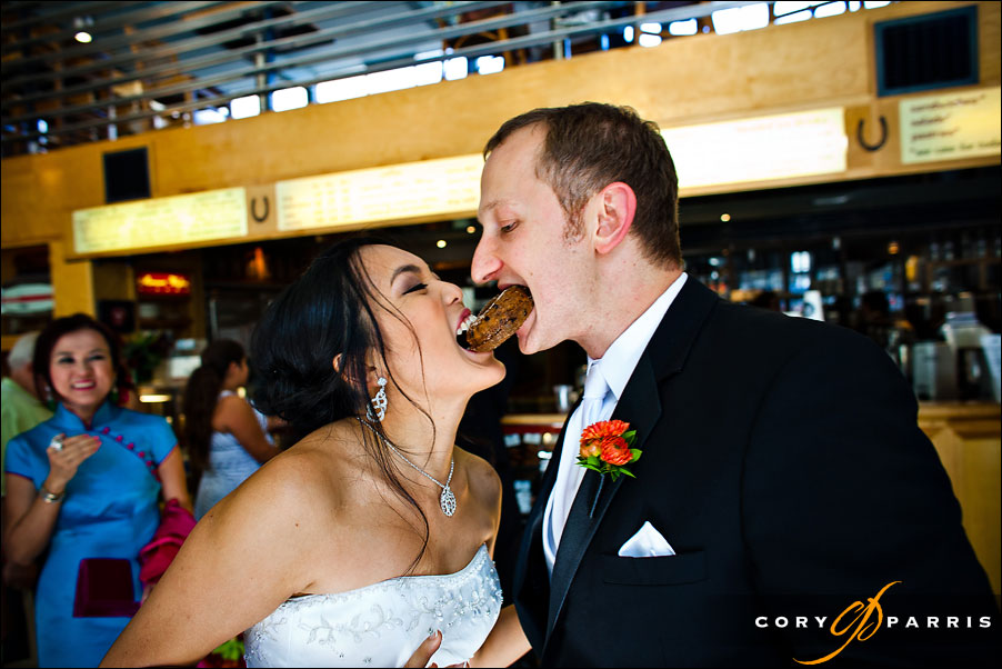 bride and groom sharing doughnut at top pot by seattle wedding photographer cory parris