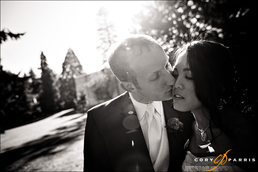 groom kissing bride with sunflare by seattle wedding photographer cory parris