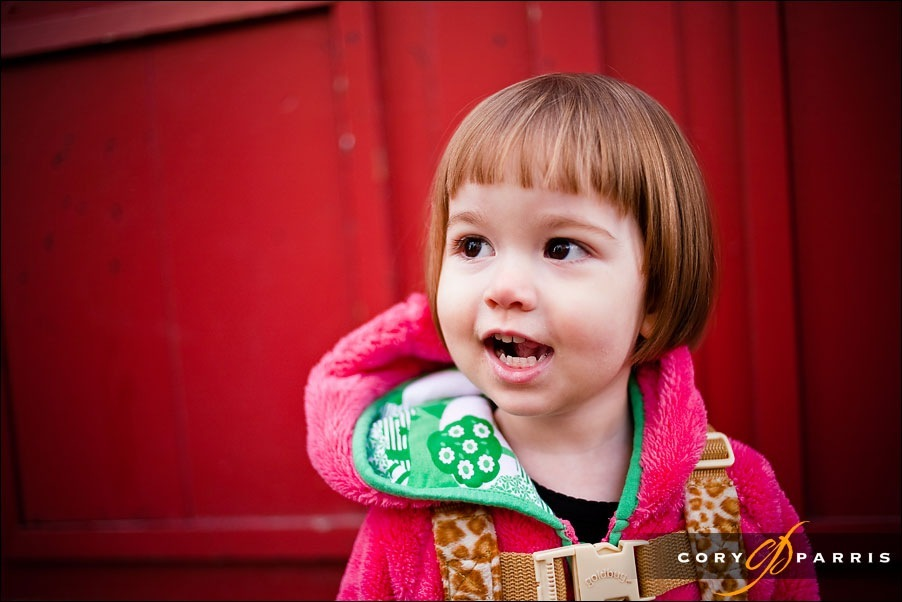smiling little girl by red door by seattle portrait photographer cory parris