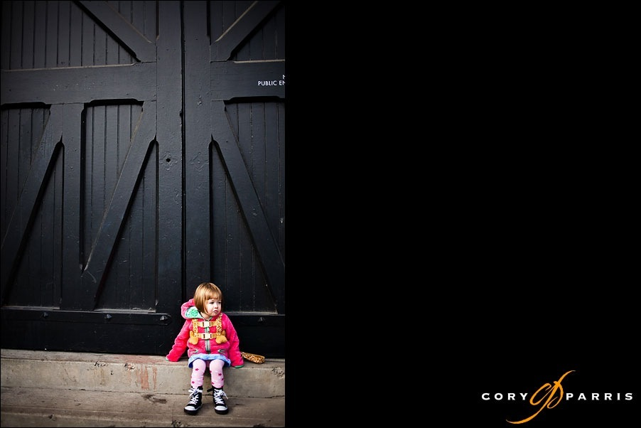 smiling little girl by black door by seattle portrait photographer cory parris