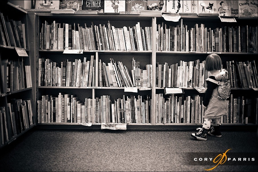 little girl looking at books seattle portrait photographer cory parris