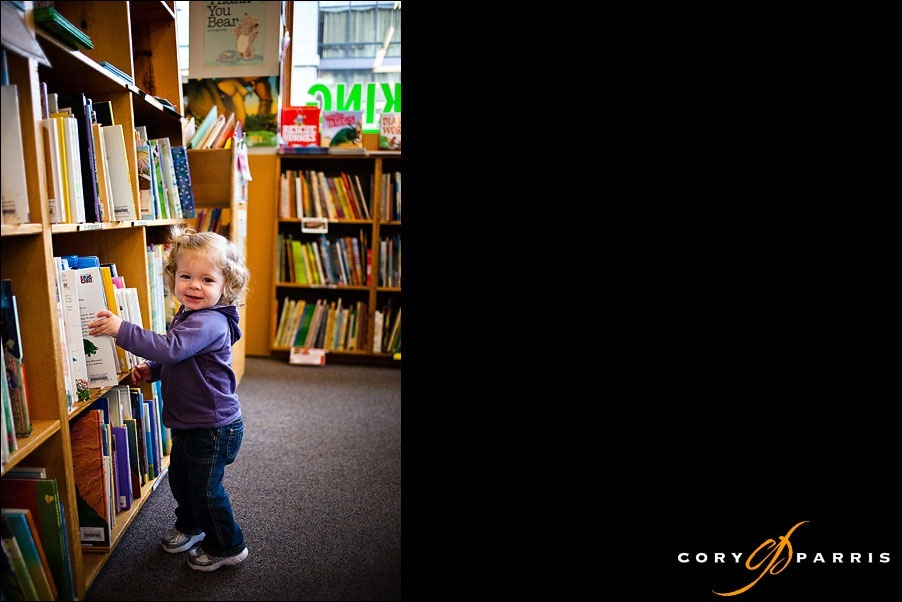 little girl choosing a book to read by seattle portrait photographer cory parris