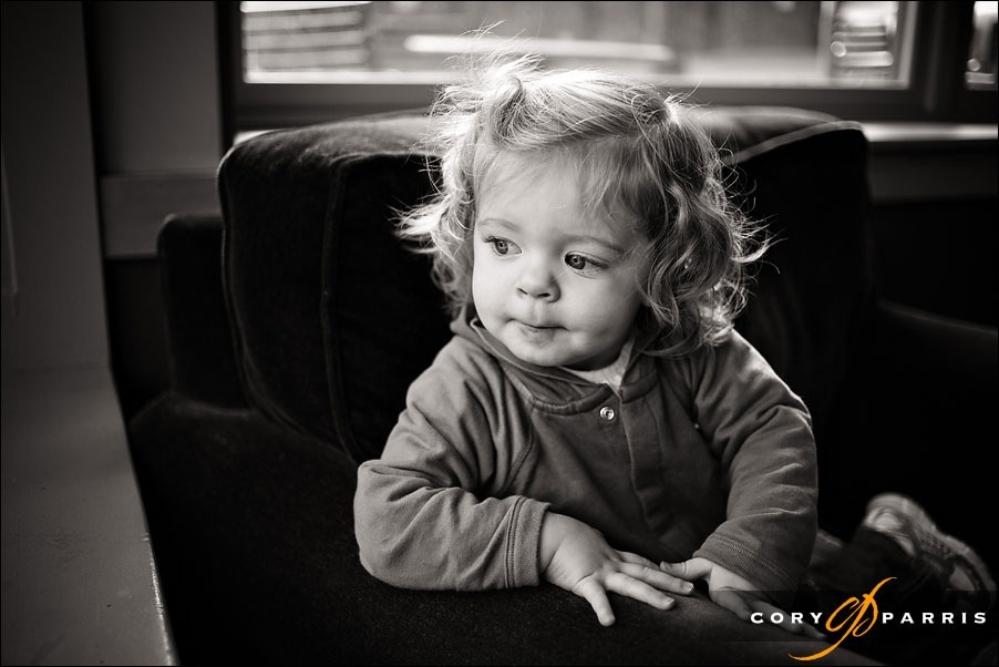 b&w portrait of a little girl in a chair looking out a window at Starbucks by seattle portrait photographer