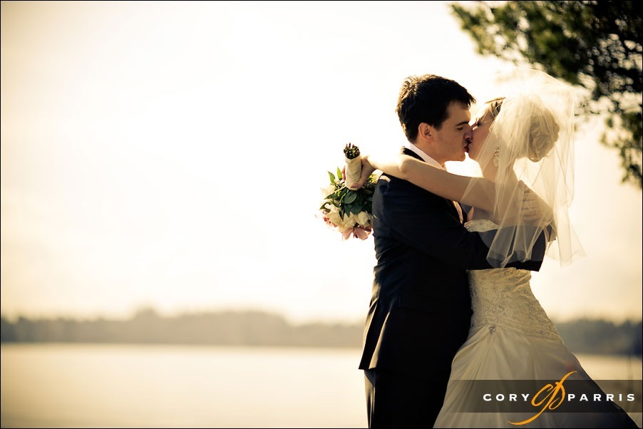 bride and groom kissing at the kirkland waterfront by seattle wedding photographer cory parris