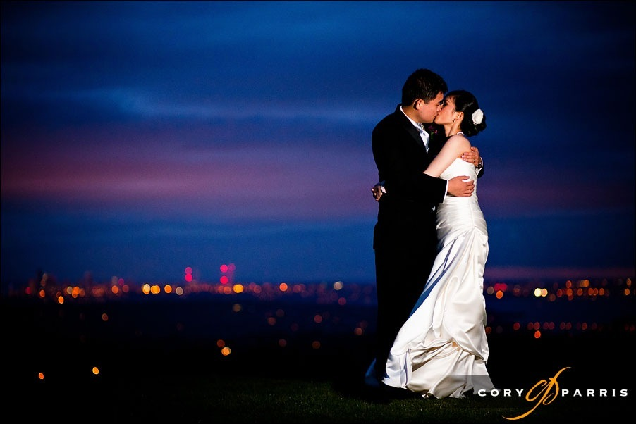bride and groom kissing on the hill at newcastle golf club with the lights of seattle behind them
