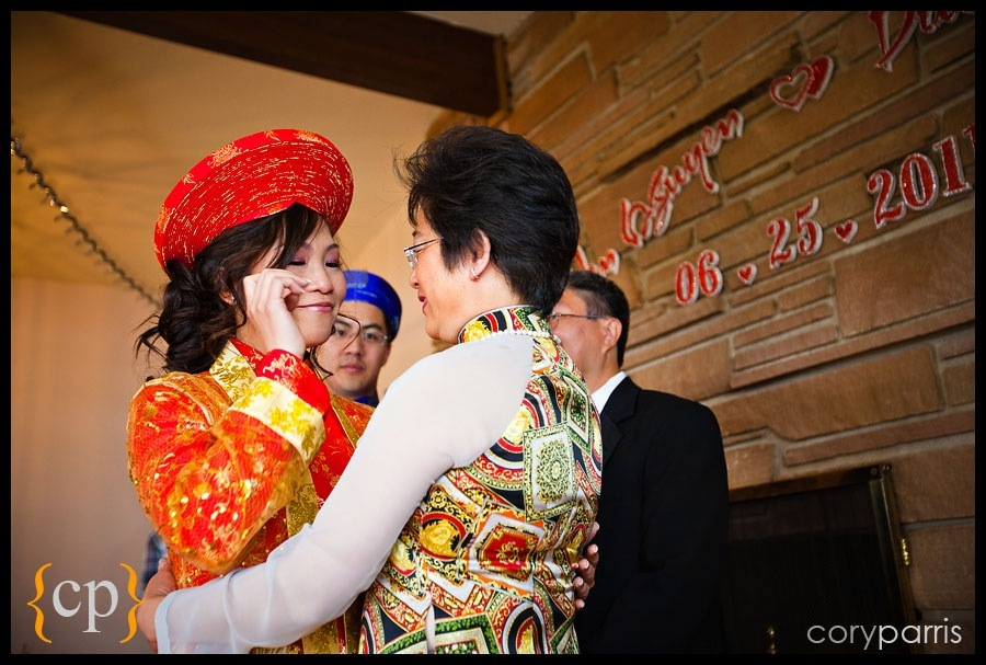 bride in traditional vietnamese dress crying as she hugs her new mother in law