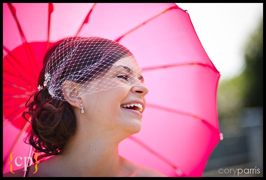 bride laughing with bright umbrella by seattle wedding photographer cory parris