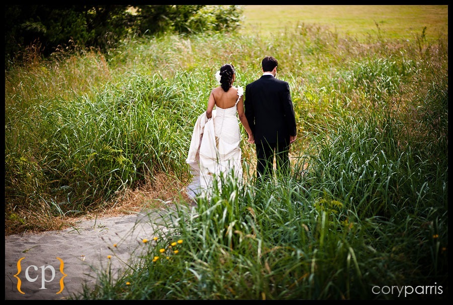 bride and groom walking away through the tall beach grasses