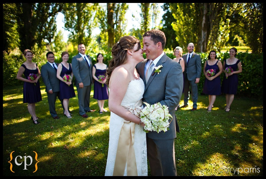 bride and groom kissing and laughing with the wedding party by seattle wedding photographer cory parris
