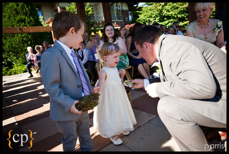 `ring bearer and flower girl coming down the aisle and being met with candy from the groom
