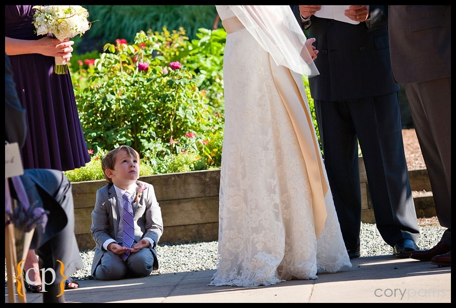 ring bearer looks up at the bride and groom during the ceremony