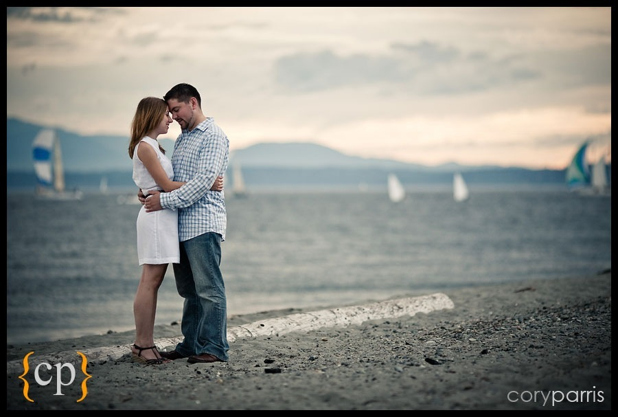 beach engagement portrait in seattle with sail boats by photographer cory parris